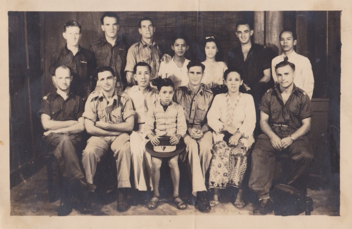 Two generations of the Ang family posing in a group photograph with British soldiers at River Valley Road Camp, Singapore, 1946